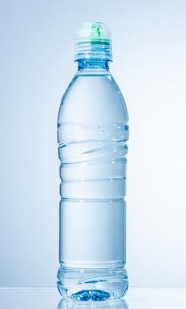 Botella de agua de plástico sobre fondo azul claro Foto de archivo