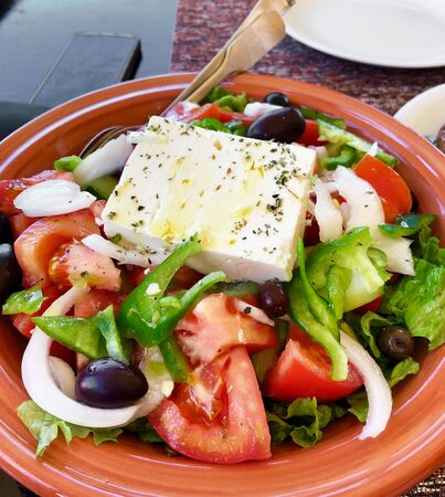 Portion of traditional greek salad on restaurant table