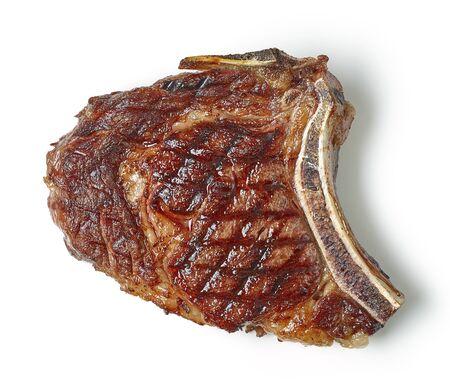 Bistecca di manzo alla griglia isolata su sfondo bianco, vista dall'alto