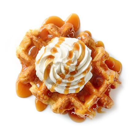 freshly baked belgian waffle decorated with cream and caramel sauce isolated on white background, top view Standard-Bild