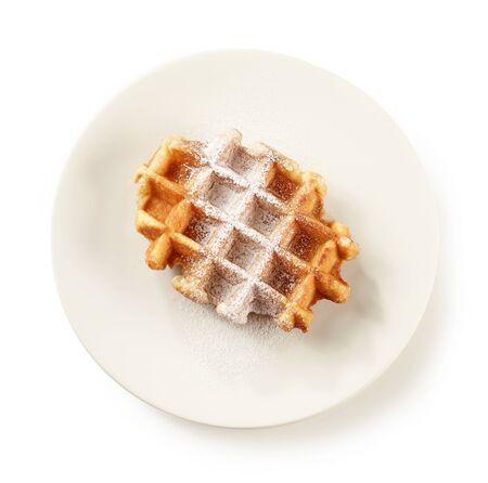 gaufre belge fraîchement préparée avec du sucre en poudre sur une plaque blanche isolée sur fond blanc, vue de dessus