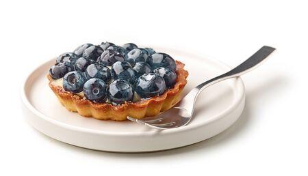 blueberry tart on white plate isolated on white background