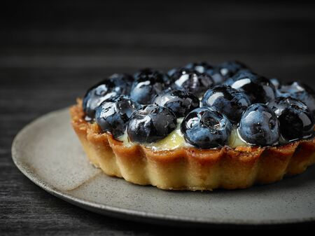 close up of blueberry tart on dark wooden table