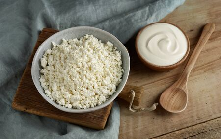 bowl of cottage cheese and sour cream on wooden kitchen table