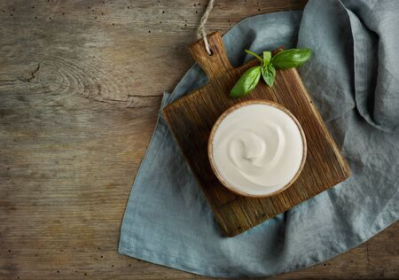bowl of sour cream on old wooden kitchen table, top view
