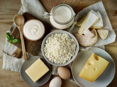 various dairy products on old wooden table, top view