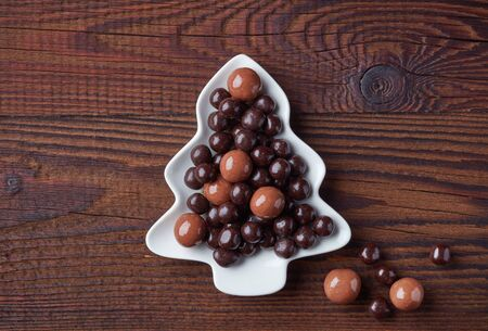Berries covered with chocolate on fir shape plate, christmas snack on wooden table, top view