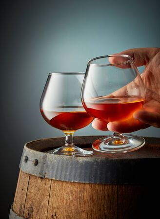 two glasses of cognac on old wooden barrel Reklamní fotografie