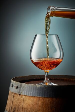 cognac pouring into glass on old wooden barrel