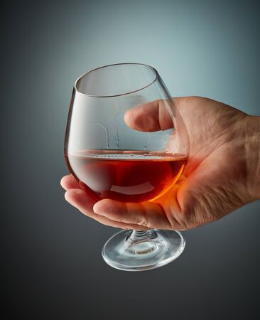 glass of cognac in human hand on grey background