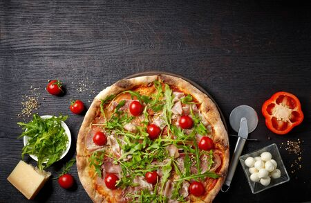 freshly baked pizza and ingredients on dark wooden table, top view