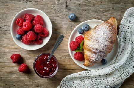 sweet croissant and berries on old wooden kitchen table, top view Banque d'images