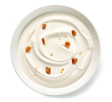 A bowl of yogurt or sour cream with small caramel pieces, top view