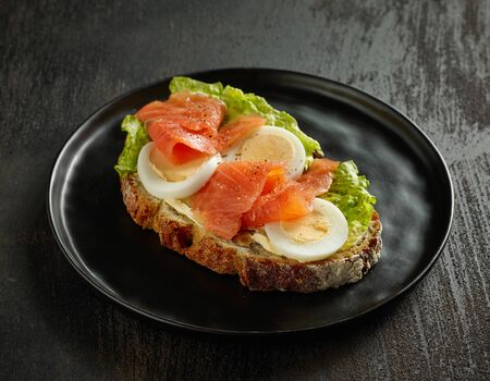 slice of bread with boiled egg and salmon on black plate