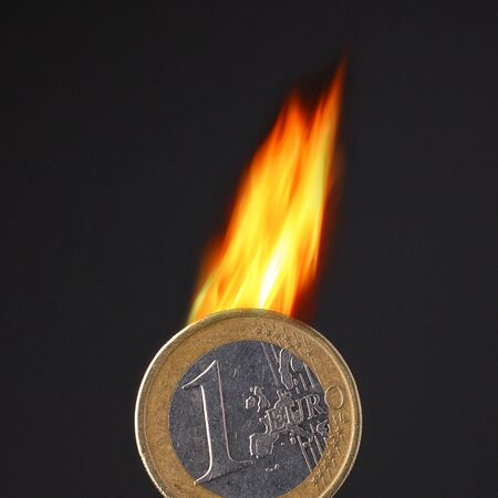 burning euro coin on black background