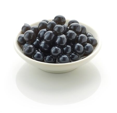 Bowl of black tapioca pearls for bubble tea isolated on white background