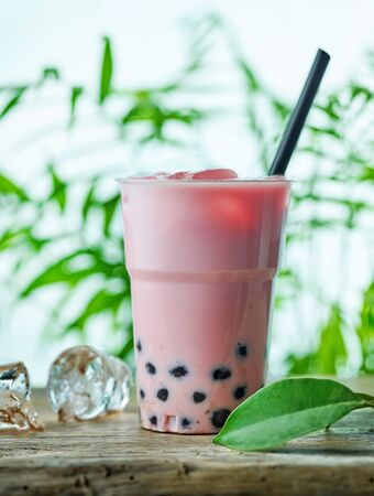 A plastic cup of iced bubble tea on wooden table
