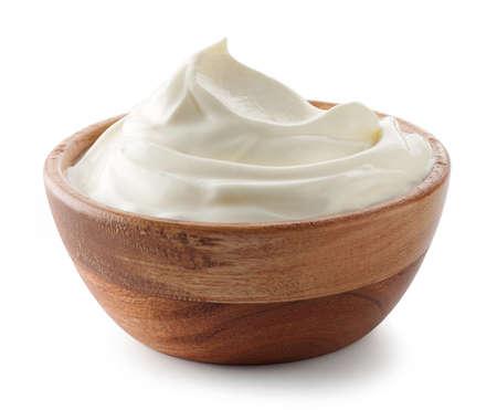 wooden bowl of whipped sour cream yogurt isolated on white background Stockfoto
