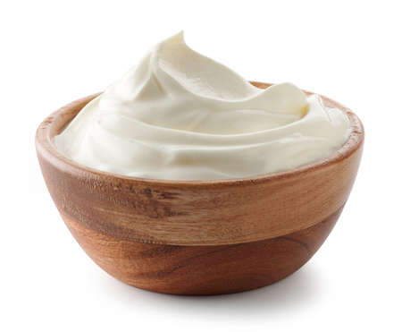 wooden bowl of whipped sour cream yogurt isolated on white background Foto de archivo