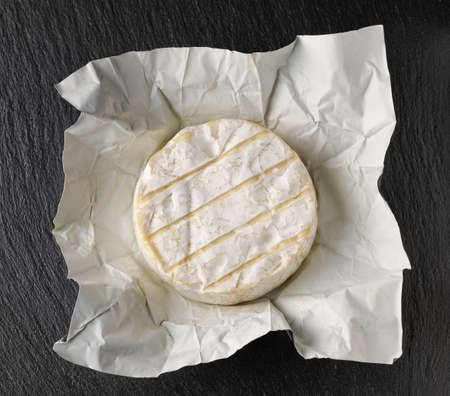 fresh brie cheese on black stone board background, top view