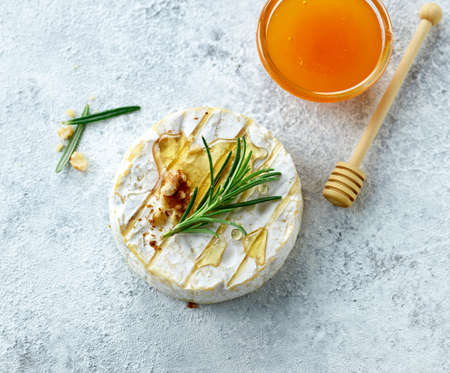 still life with fresh brie cheese, rosemary and honey, top view