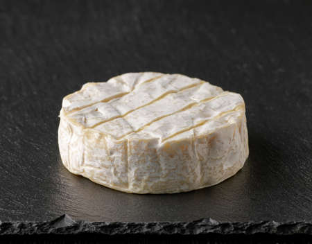 fresh brie cheese on black stone board background