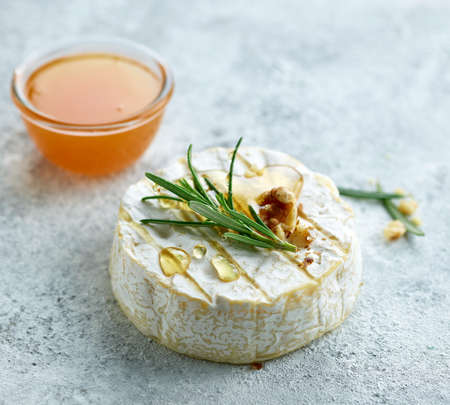 still life with fresh brie cheese, rosemary and honey
