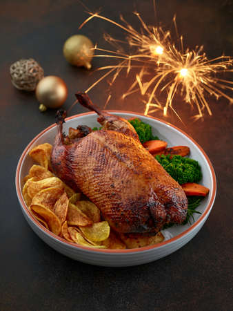 freshly roasted duck roast with vegetables in white ceramic serving bowl and christmas lights