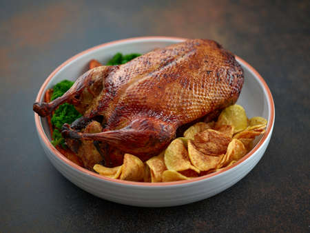freshly roasted duck roast and vegetables in serving bowl