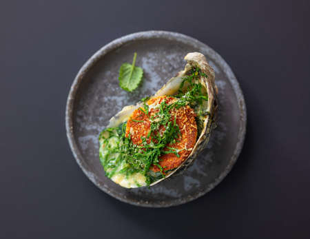 baked oyster with toasted bread and greens on grey plate, top view, selective focus