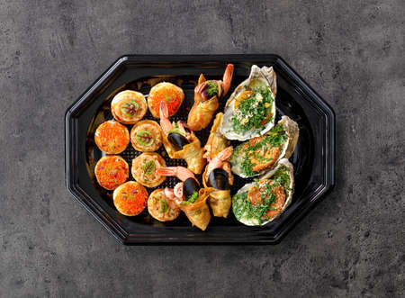 plate of various seafood snacks on grey table, top view