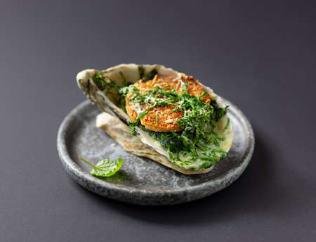 baked oyster with toasted bread and greens on grey plate, selective focus