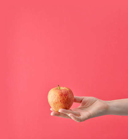 fresh apple in human hand isolated on pink background