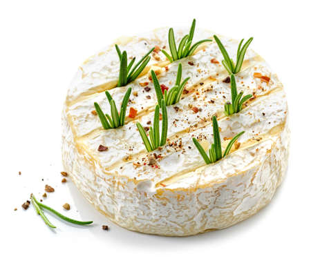 fresh whole brie cheese with rosemary and spices ready for baking isolated on white background 免版税图像