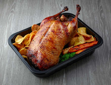 duck roast and vegetables in plastic take away container on grey table 免版税图像