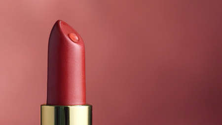 closeup of red moisturizing lipstick with drop of oil macro