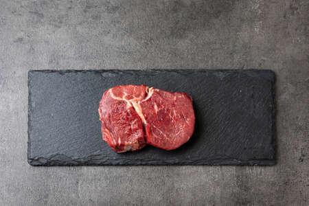 fresh raw beef steak meat on black stone background