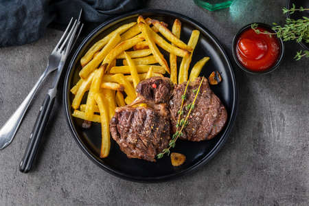 freshly grilled beef steak meat and french fries on black plate, top view