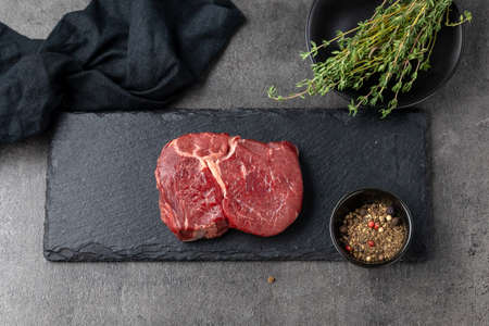 fresh raw beef steak meat on black stone background, top view