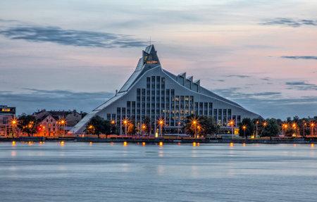 Riga, LATVIA - SEPTEMBER 11, 2020: night view of Latvian National library on the bank of the Daugava river