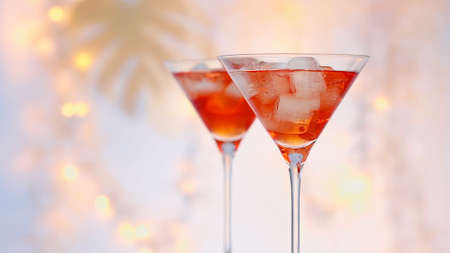 two glasses of red summer cocktail with ice cubes close up, defocused  festive lights in background