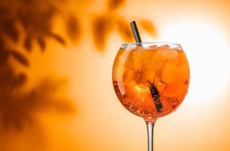 glass of orange  cocktail on defocused leaves background