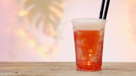 fresh pink soft drink in plastic take away cup with ice cubes, defocused palm leaf and gold lights in background Reklamní fotografie
