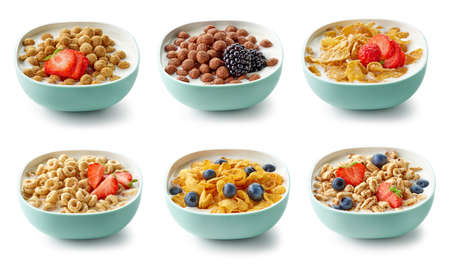 various bowls of breakfast cereal with milk and berries isolated on white background