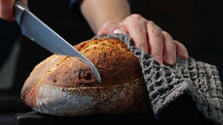 cook slicing freshly baked bread on black wooden cutting board
