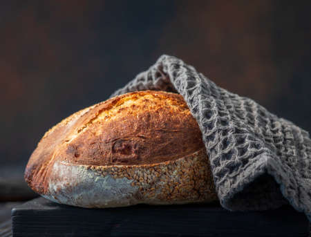 freshly baked bread covered with grey towel on black wooden cutting board