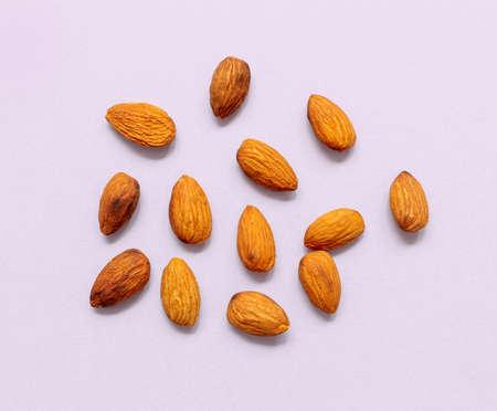 almonds on light purple paper background, top view Reklamní fotografie