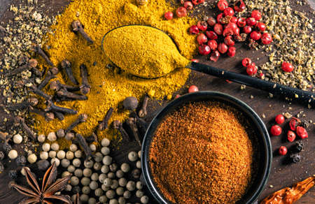 various spices on wooden table close up top view