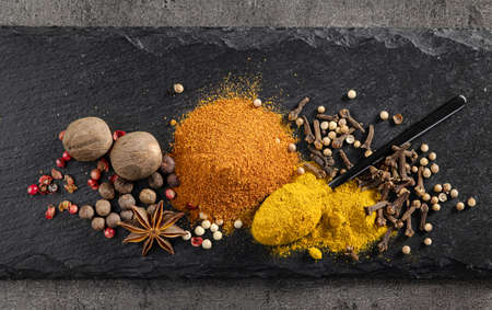 various spices on black plate top view composition