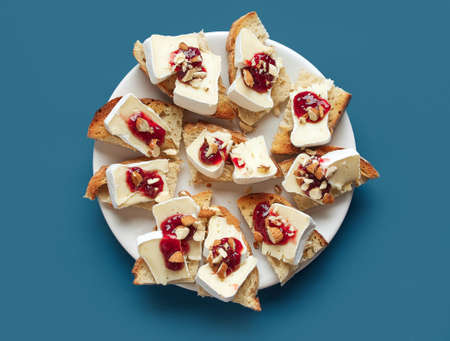 plate of toasted bread slices with fresh brie cheese on blue background, top view